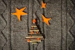 与新年树装饰的圣诞节温暖的被编织的背景由棍子制成 葡萄酒与手工制造圣诞节tr的圣诞卡 库存照片