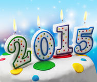 与新年的标志的灼烧的蜡烛在蛋糕的2015年 免版税库存照片