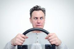 与方向盘的斗眼的滑稽的人司机 免版税库存图片