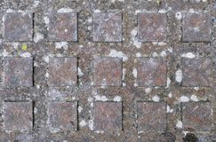 与方形的外形的生锈的人孔盖作为背景、纹理或者细节 库存图片
