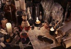 与方术纸、葡萄酒瓶、蜡烛和魔术的神秘的静物画反对 免版税库存图片
