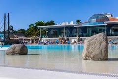 与旅游太阳沐浴者的一个旅馆水池有两块石头的在水e中 图库摄影