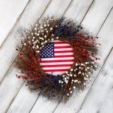 与旗子的美国独立日花圈在土气白色木板 图库摄影