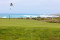 与旗子的美好的高尔夫球孔绿色在加利福尼亚海洋海岸 免版税库存照片