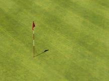 与旗子的高尔夫球孔从上面 库存照片