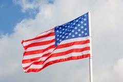 与旗杆的美国国旗在清楚的蓝天backgrou 免版税库存照片