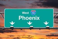 与日出天空的菲尼斯亚利桑那跨境10西部高速公路标志 库存照片