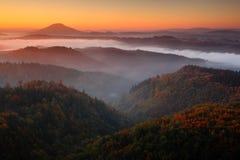 与日出的冷的有薄雾的有雾的早晨在漂泊瑞士公园秋天谷  与雾,捷克的风景的小山, 库存图片