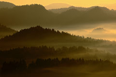 与日出的冷的有薄雾的有雾的早晨在漂泊瑞士公园秋天谷  与雾,捷克的风景的小山, 库存照片