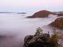 与日出的满月夜在一座美丽的山 从大雾增加的五颜六色的秋天小山 免版税库存图片