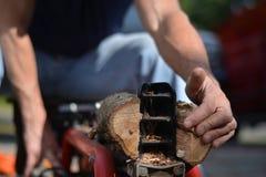 与日志分离机的人分裂的木头 免版税库存图片