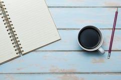 与日志和铅笔的咖啡在木地板上 免版税库存照片