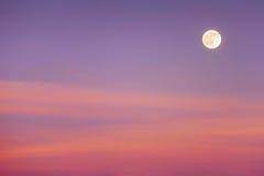 与日落云彩的满月 免版税库存图片