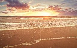 与日落和云彩的海滩在金黄小时和海水流量 免版税图库摄影
