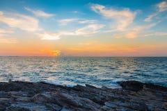 与日落地平线的岩石海岸线在海洋 库存图片