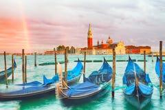 与日落天空、彩虹和长平底船的五颜六色的风景在广场圣Marco附近停放了在威尼斯 圣乔治Maggiore教会  免版税库存图片