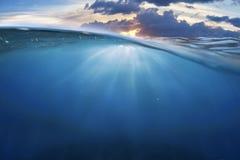 与日落天空的海洋半水 免版税图库摄影
