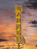 与日落天空的葡萄酒霓虹车库箭头标志 库存图片