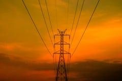与日落天空的高压电定向塔 免版税库存照片