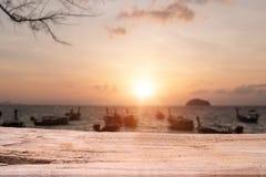 与日落时间的木桌在海海滩橙色和温暖的口气 免版税库存图片