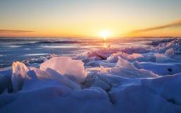 与日落火热的天空和冻湖的美好的冬天风景 免版税库存图片