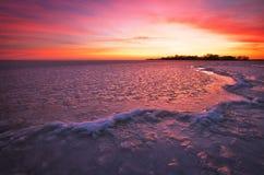 与日落火热的天空和冻河的冬天风景 库存照片
