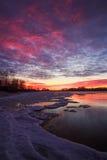 与日落火热的天空和冻湖的冬天风景 免版税图库摄影