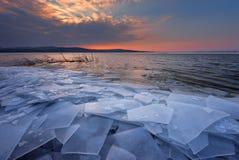 与日落火热的天空和冻湖的美好的冬天风景 本质的构成 免版税库存图片