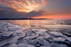 与日落火热的天空和冻湖的美好的冬天风景 本质的构成 库存图片