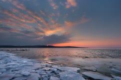 与日落火热的天空和冻湖的美好的冬天风景 本质的构成 图库摄影