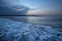 与日落火热的天空和冻湖的美好的冬天风景 本质的构成 库存照片