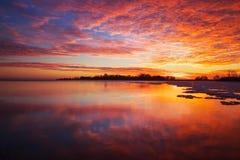 与日落火热的天空和冻湖的美好的冬天风景 库存图片