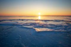 与日落火热的天空和冻湖的美好的冬天风景 库存照片