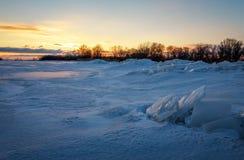 与日落火热的天空和冻湖的美好的冬天风景 免版税库存照片