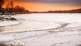 与日落火热的天空的冬天风景,在冻河 免版税库存照片