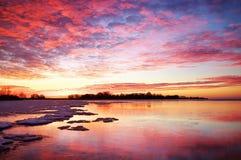 与日落火热的天空的冬天风景 免版税库存照片