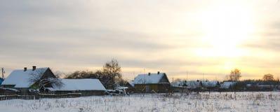与日落的冬天农村风景 免版税图库摄影