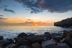 与日落的多岩石的海滩在海岸地平线背景 免版税库存图片