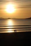 与日落的夫妇走的海滩 免版税库存图片