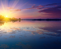 与日落的好的风景在湖 免版税库存图片