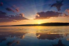与日落的好的风景在湖 免版税库存照片