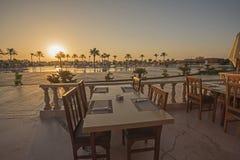 与日落的室外餐桌在热带旅馆手段 库存图片