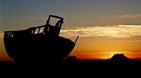 与日落的小船剪影在后面地面 免版税图库摄影