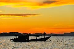 与日落的小船 免版税库存图片