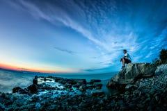 与日落的美好的风景在湖和一个年轻人坐岩石 库存图片