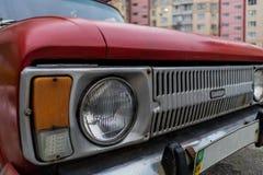 与日落的老汽车hedlight在背景 免版税库存图片