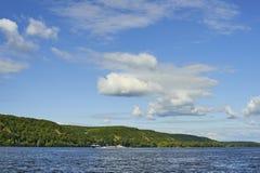 与日间小山和云彩的河风景 免版税库存照片
