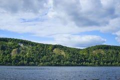 与日间小山和云彩的河风景 库存图片