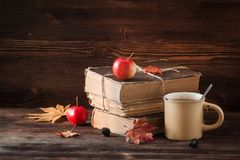 与旧书、苹果、槭树叶子和一杯咖啡的秋天静物画在木背景的 免版税库存照片
