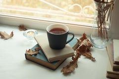 与旧书、茶和蜡烛的温暖和舒适场面在桌上 秋天周末,秋天生活方式 免版税库存照片